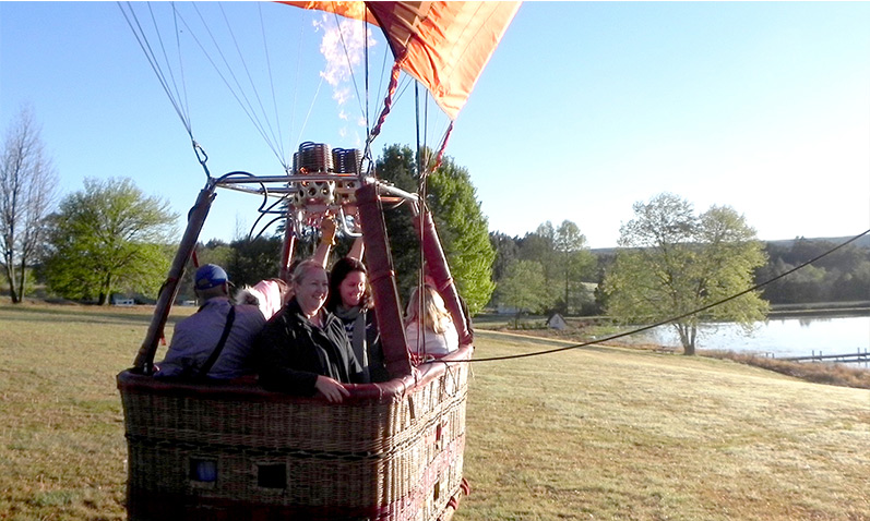 Pilot and passengers about to take off for a hot air balloon flight.